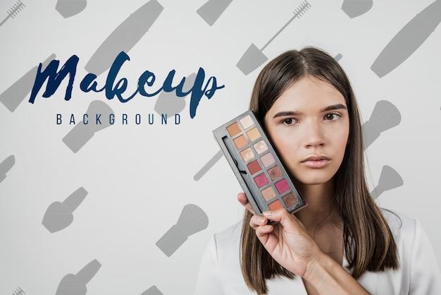 Vista frontal da menina com paleta de maquiagem