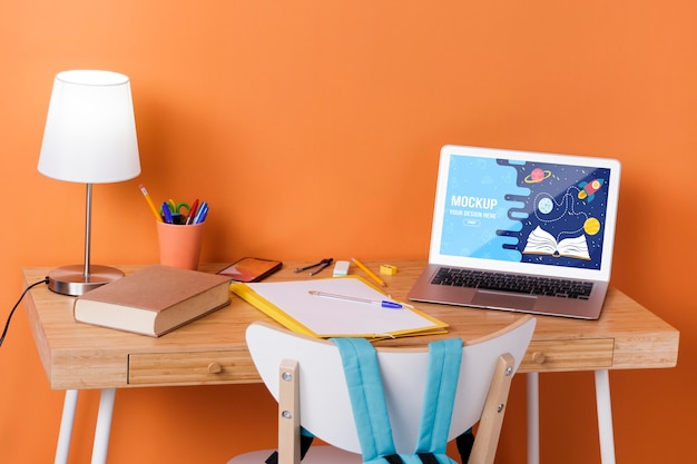 Vista frontal da mesa com fundamentos da escola e laptop