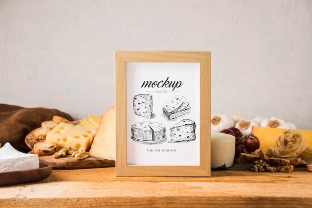 Vista frontal da moldura com variedade de queijos e uvas