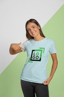 Vista frontal da mulher, apontando para a camiseta que ela está vestindo