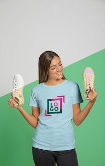 Vista frontal da mulher de camiseta segurando tênis