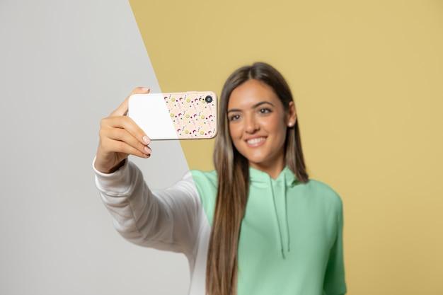 Vista frontal da mulher de capuz tomando selfie com smartphone