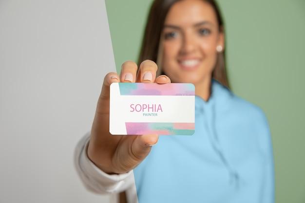 Vista frontal da mulher mostrando o cartão de visita