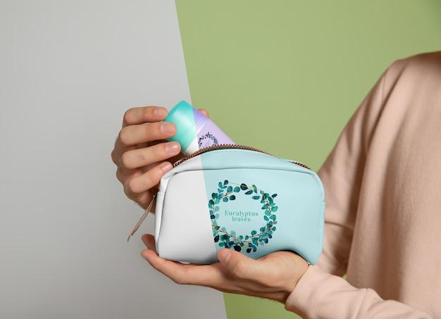 Vista frontal da mulher segurando a bolsa de maquiagem