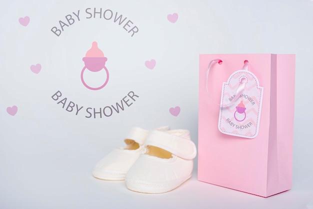 Vista frontal da sacolinha rosa com sapatos para chá de bebê
