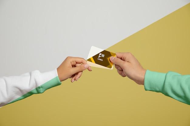 Vista frontal das mãos segurando cartões de visita