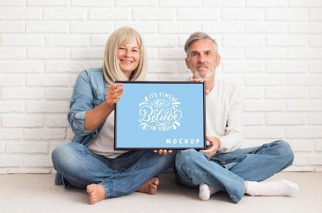 Vista frontal de casal segurando uma maquete de moldura
