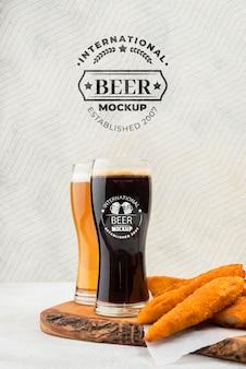 Vista frontal de copos de cerveja com salgadinhos