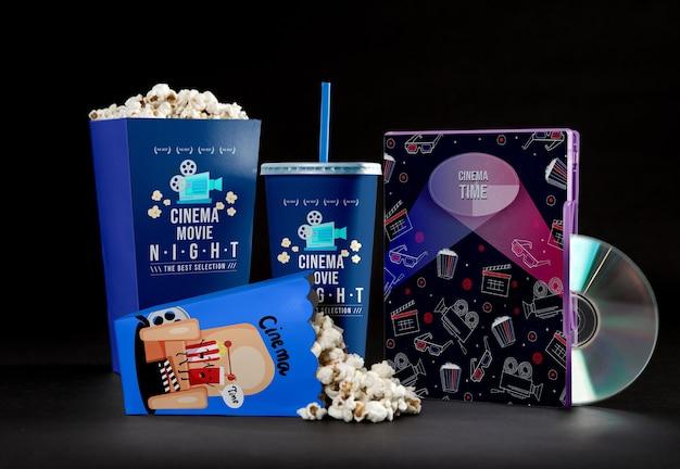 Vista frontal de copos de pipoca de cinema com palha e dvd