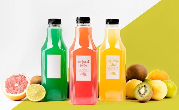 Vista frontal de garrafas de suco com toranja e kiwi
