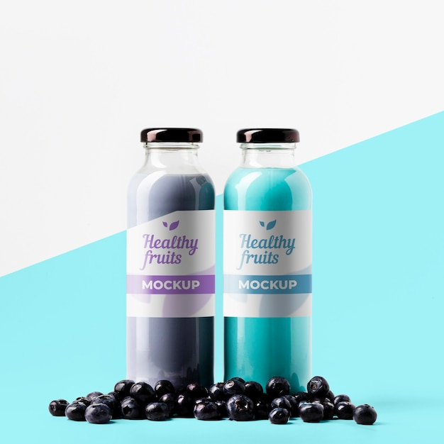 Vista frontal de garrafas de suco transparentes com mirtilos