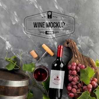 Vista frontal de garrafas de vinho e copo com uvas