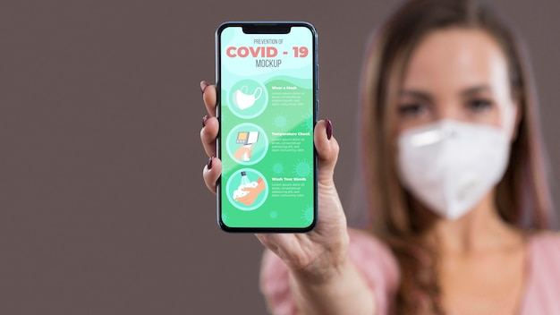 Vista frontal de mulher com máscara segurando smartphone