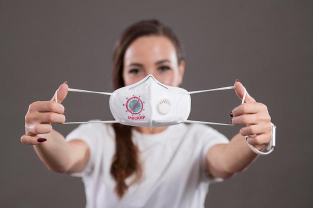 Vista frontal de mulher segurando uma máscara Psd grátis