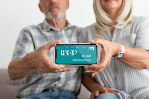Vista frontal de um homem e uma mulher segurando um smartphone