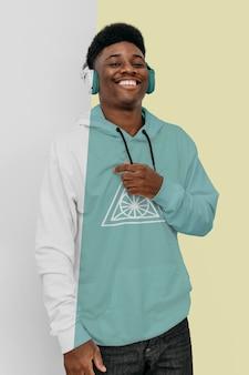 Vista frontal de um homem estiloso com capuz e fones de ouvido