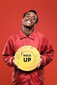 Vista frontal de um homem feliz segurando o disco de vinil para a maquete de loja de música