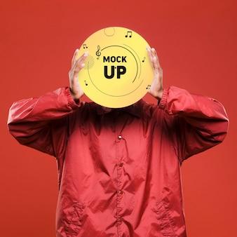 Vista frontal de um homem segurando um disco de vinil sobre o rosto para uma maquete de loja de música