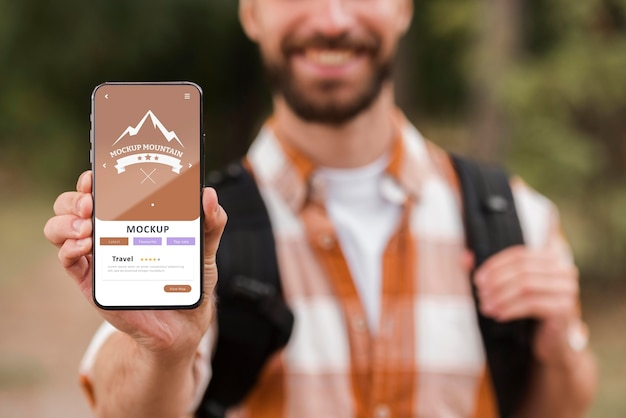 Vista frontal de um homem sorridente segurando um smartphone enquanto acampa