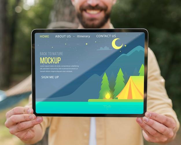 Vista frontal de um homem sorridente segurando um tablet enquanto acampa