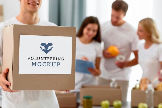 Vista frontal de um voluntário masculino segurando uma caixa com doações