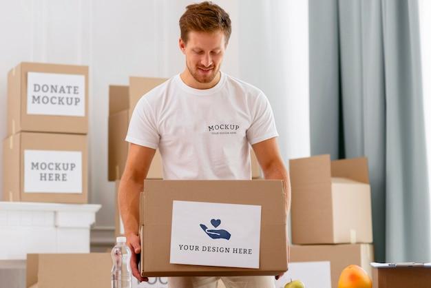 Vista frontal de um voluntário segurando uma caixa de doações