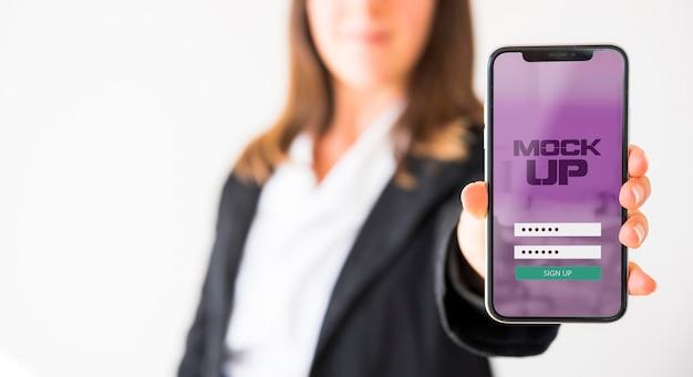 Vista frontal de uma empresária segurando um smartphone