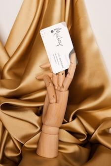 Vista frontal de uma mão de madeira segurando um cartão de visita