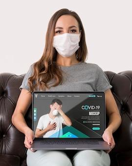 Vista frontal de uma mulher com máscaras segurando um laptop enquanto está sentada no sofá