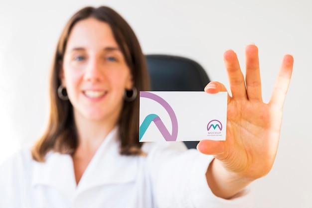 Vista frontal de uma mulher de negócios desfocada segurando um cartão de visita