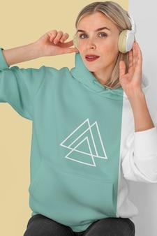 Vista frontal de uma mulher elegante com capuz e fones de ouvido