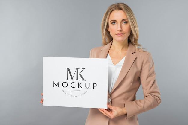 Vista frontal de uma mulher elegante segurando um cartaz em branco