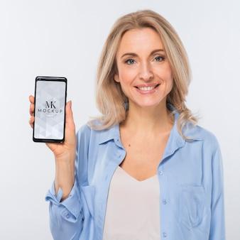 Vista frontal de uma mulher loira sorridente segurando um smartphone