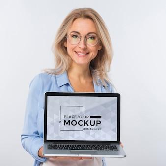 Vista frontal de uma mulher sorridente com óculos segurando um laptop