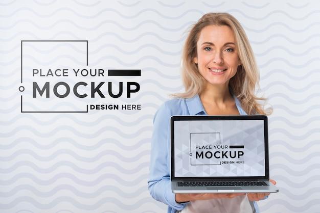 Vista frontal de uma mulher sorridente segurando um laptop