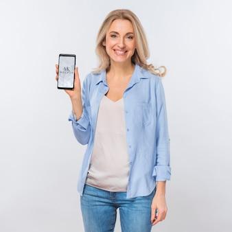 Vista frontal de uma mulher sorridente segurando um smartphone