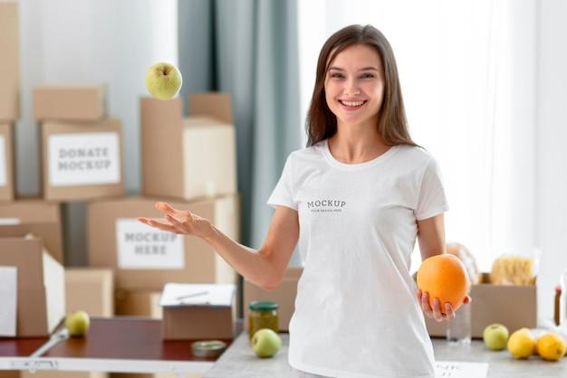Vista frontal de uma voluntária sorridente jogando maçã para o alto