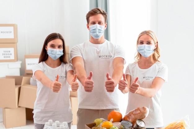Vista frontal de voluntários com máscaras médicas fazendo sinal de positivo