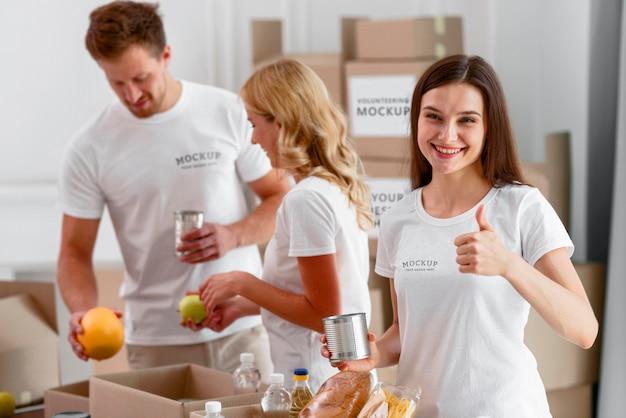 Vista frontal de voluntários segurando provisões para doação e aprovando