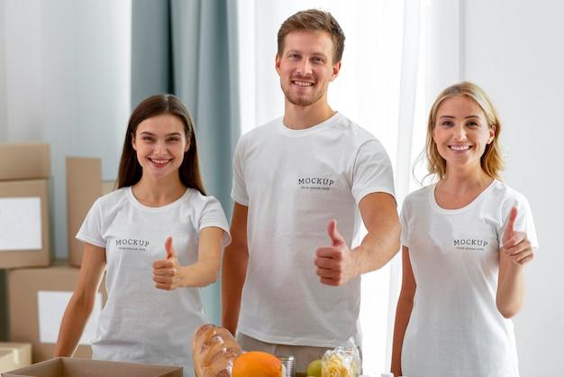 Vista frontal de voluntários sorridentes fazendo sinal de positivo