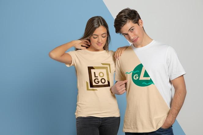 Vista frontal do casal posando em camisetas