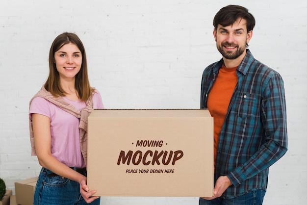 Vista frontal do casal segurando a maquete da caixa em movimento