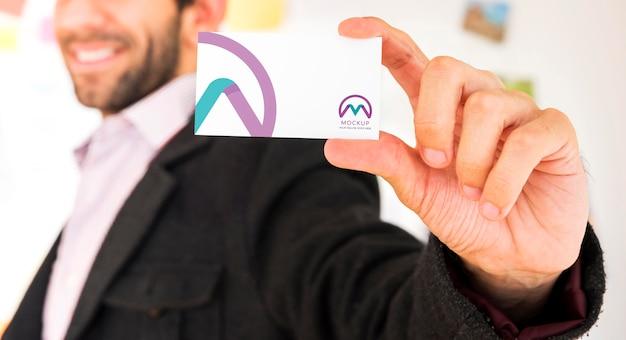 Vista frontal do empresário desfocado segurando um cartão de visita