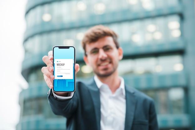 Vista frontal do empresário segurando um smartphone