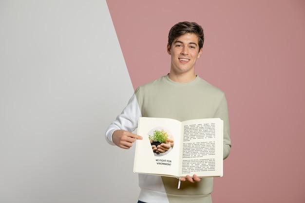 Vista frontal do homem apontando para o livro que ele está segurando