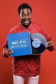 Vista frontal do homem segurando o disco de vinil para a maquete da loja de música