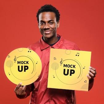 Vista frontal do homem sorridente segurando o disco de vinil para a maquete da loja de música