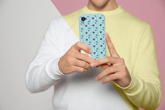 Vista frontal do homem tirando uma foto com o smartphone