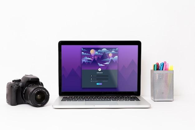 Vista frontal do laptop com câmera e canetas na mesa