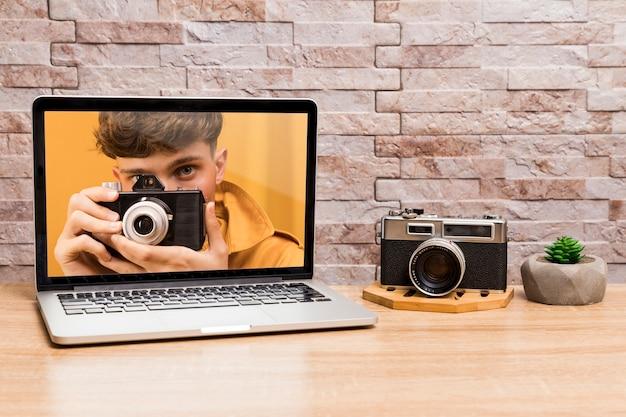 Vista frontal do laptop e câmera na mesa